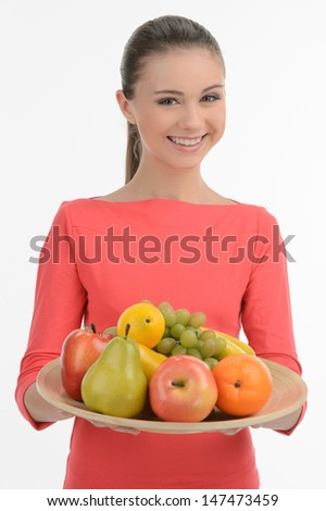Teenage girl with fruits. Happy teenage girl holding a plate with fruits while standing isolated on white