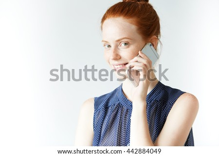 Teenage girl with ginger hair and green eyes wearing dot dress, making phone calls, inviting her friends for her birthday party, looking and smiling at the camera with happy and cheerful expression - stock photo
