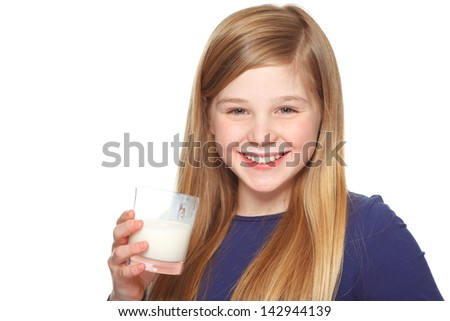 teenage girl with glass of milk and milk mustache smiling - stock photo