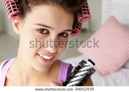 Teenage girl with hair in curlers - stock photo