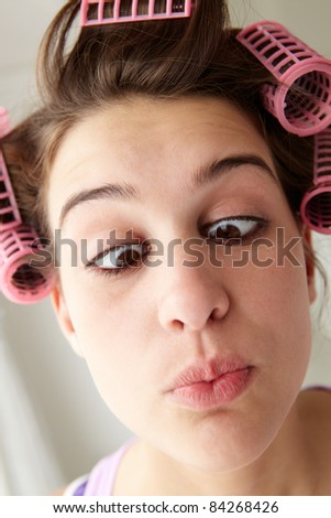 Teenage girl with hair in curlers pulling a face - stock photo