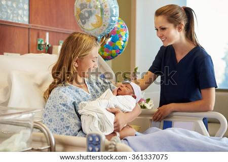 Teenage Girl With Nurse Holding Newborn Baby In Hospital - stock photo