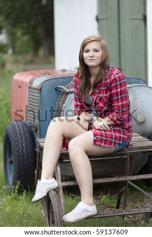Teenage girl with red shirt sitting down on an old farms table - stock photo