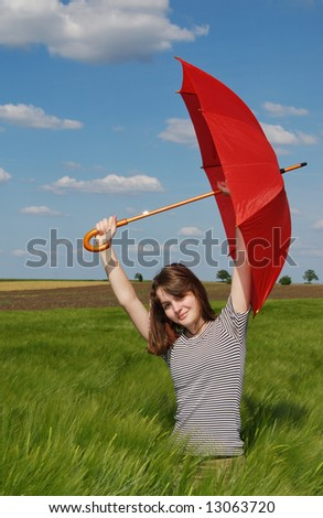 Teenage girl  with red umbrella in green wheat field