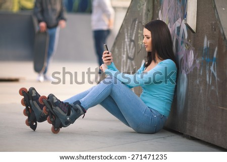 Teenage girl with rollerblades sitting on the floor in skate park and using mobile phone - stock photo