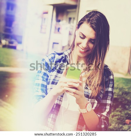 Teenage girl with smartphone and earphones smiling texting. Young Caucasian woman outdoors in summer with cellphone. Retouched, filter, light leak effect, vibrant colors, square format. - stock photo