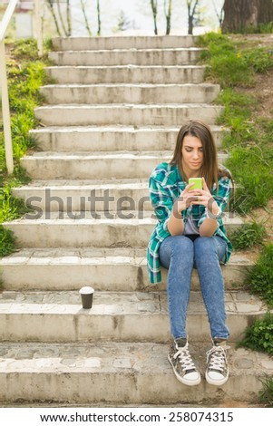 Teenage girl with smartphone and takeaway coffee outdoors in park sitting on stairs texting. Young woman in casual clothes text messaging enjoying spring day outdoors. Vertical, very mild retouch. - stock photo