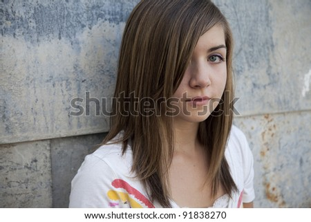 Teenage girl with somber expression against grunge wall