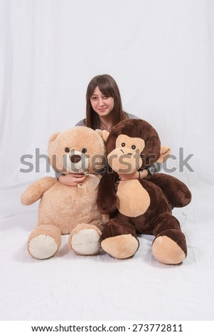Teenage girl with teddy bear and monkey