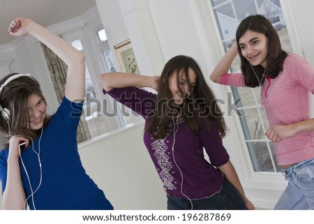 Teenage girlfriends dancing for joy to the music from headphones - stock photo
