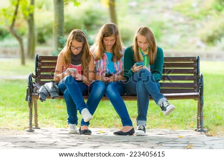 Teenage girls after school, sitting on bench and using their mobile phones - stock photo