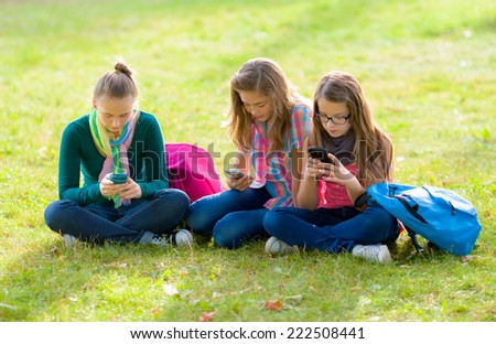 Teenage girls after school, sitting on grass in the park, using their mobile phones - stock photo