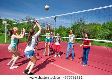 Teenage girls and boy play together volleyball - stock photo