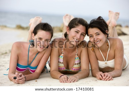Teenage girls at the beach - smiling while lying on the floor - stock photo