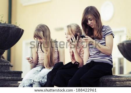 Teenage girls calling on the mobile phones - stock photo