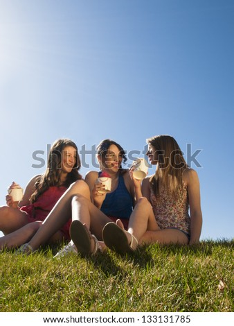 Teenage girls eating frozen soft serve yogurt. - stock photo