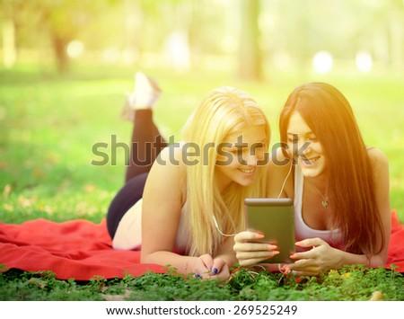 Teenage girls having fun online on digital tablet outdoors in park - stock photo