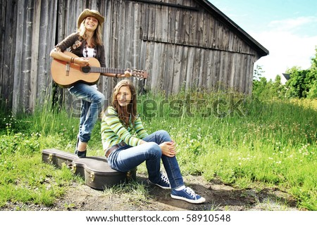Teenage girls having fun together with guitar at the farm