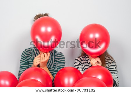 Teenage girls hiding their faces behind smiling balloons. - stock photo