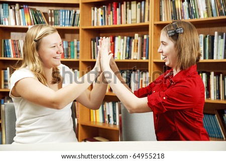 Teenage girls in the school library, giving each other high fives.
