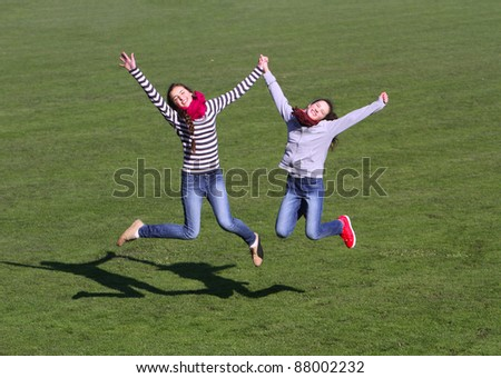 Teenage girls jumping on the stadium field grass background - stock photo