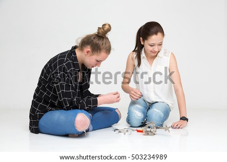 Teenage girls on the floor assembling metal helicopter model