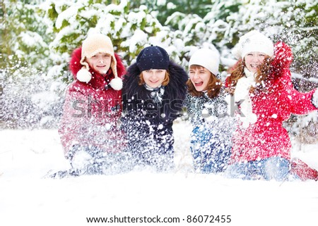 Teenage girls playing with snow in park - stock photo