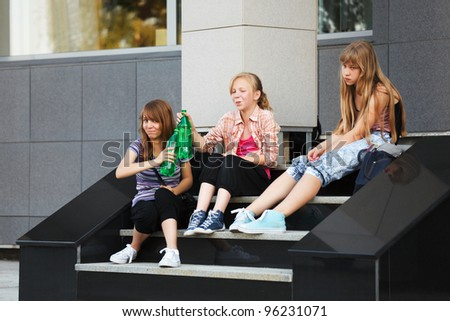 Teenage girls relaxing on a school steps - stock photo