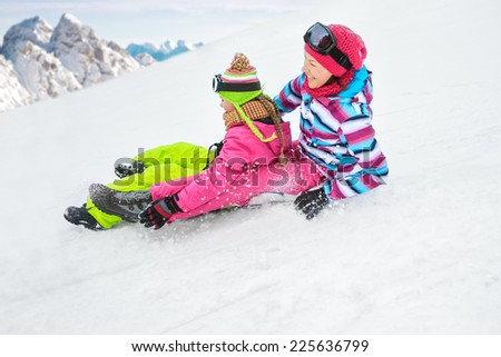 teenage girls riding sledge in the Alps - stock photo