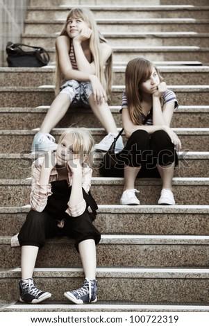 Teenage girls sitting on a steps - stock photo