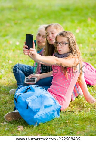 Teenage girls sitting on grass and taking selfie with mobile phone - stock photo