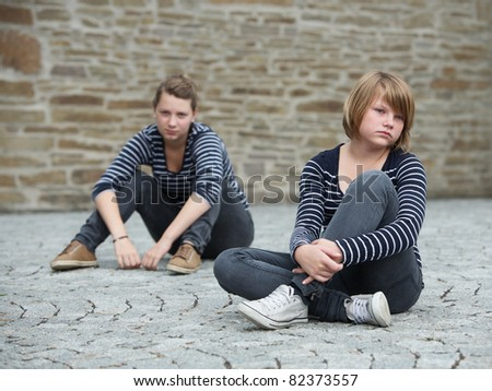 Teenage girls sitting on grounds, turned away from one another - stock photo