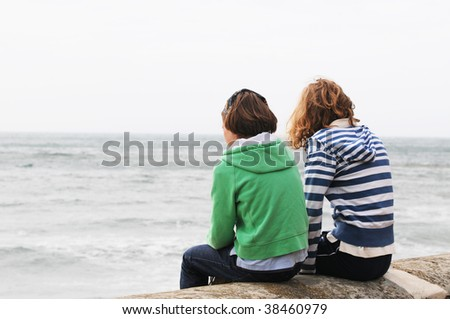 teenage girls sitting on pier looking out to sea - stock photo