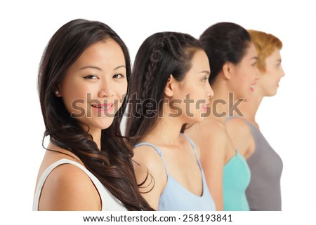 Teenage girls standing in a row, focus on foreground - stock photo