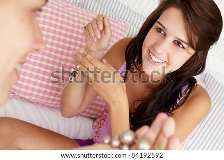 Teenage girls trying on jewellery - stock photo