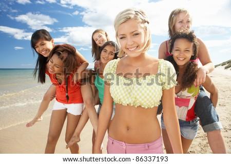 Teenage girls walking on beach - stock photo