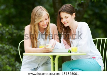 Teenage Girls With Digital Tablet And Mobile Phone In cafe - stock photo