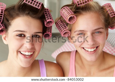 Teenage girls with hair in curlers - stock photo