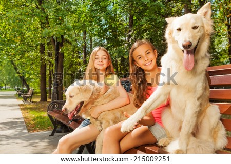 Teenage girls with their dogs on the park bench - stock photo