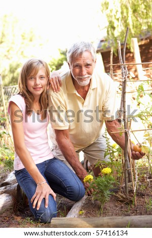 Teenage Granddaughter And Grandfather Relaxing In Garden