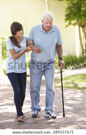 Teenage Granddaughter Helping Grandfather Out On Walk - stock photo