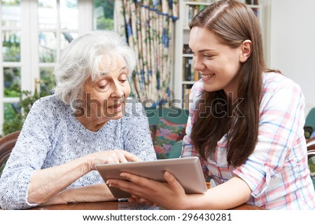 Teenage Granddaughter Showing Grandmother How To Use Digital Tablet - stock photo