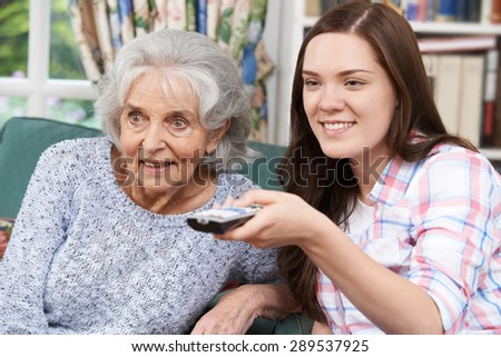 Teenage Granddaughter Watching Television With Grandmother - stock photo
