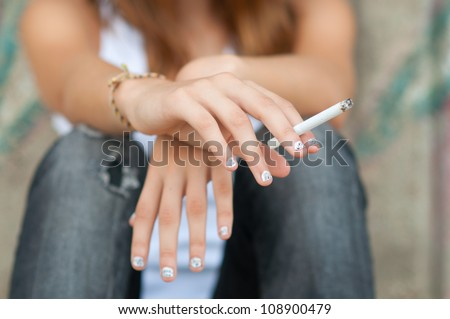 Teenage hands holding cigarette. - stock photo