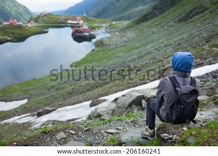 Teenage hiker boy resting nearby a lake in the mountains
