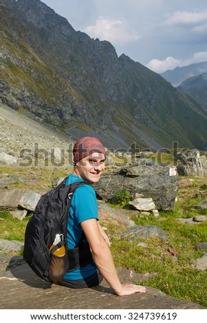 Teenage hiker with backpack resting on a rock in a mountain view - stock photo
