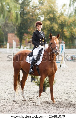 Teenage horse rider girl winning in equestrian competition. Young happy sportswoman with first place medal - stock photo