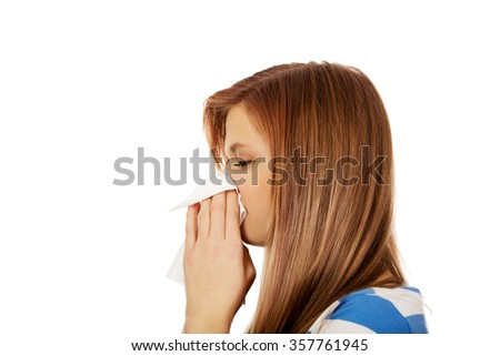 Teenage ill woman using a tissue. - stock photo