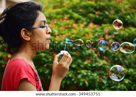 Teenage Indian girl blowing soap bubbles in the park.