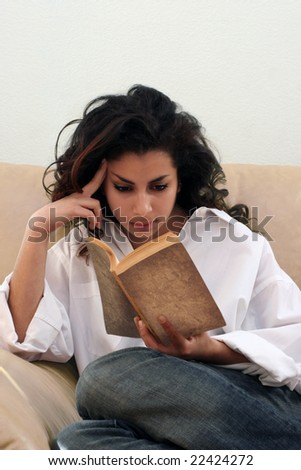 Teenage indian girl reading a book on a sofa - stock photo